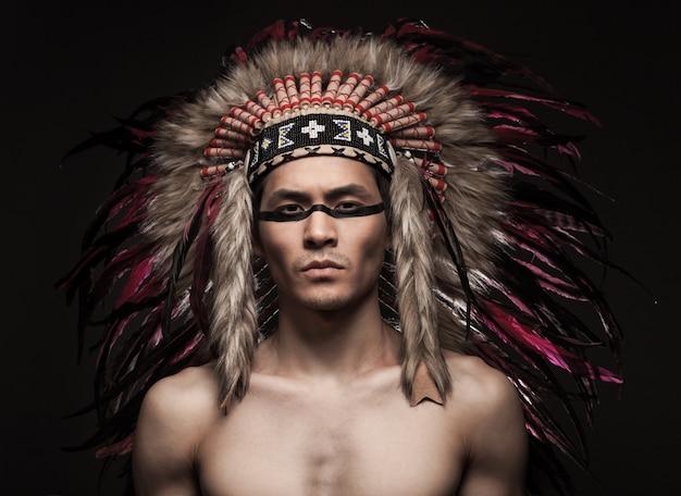 Retrato del hombre fuerte indio posando con maquillaje tradicional nativo americano