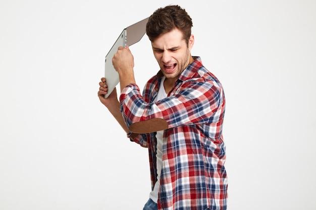 Retrato de un hombre furioso enojado lanzando su computadora portátil