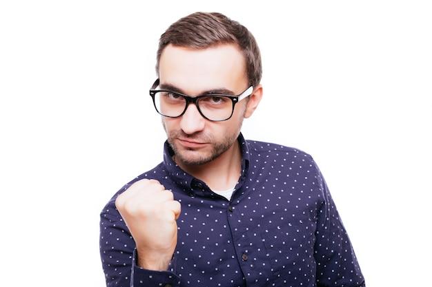Retrato de un hombre furioso enojado que amenaza con un puño aislado sobre la pared blanca