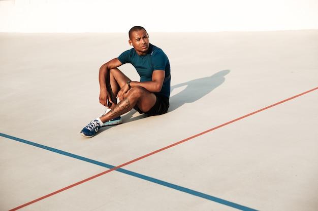 Retrato de un hombre de gimnasio africano cansado en auriculares descansando