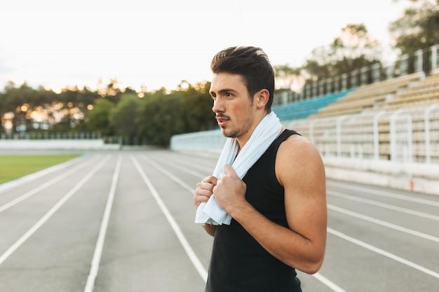 Retrato de un hombre de gimnasio con una toalla sobre los hombros