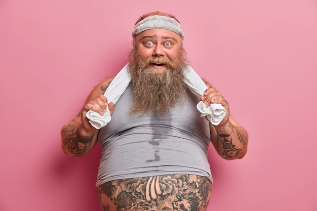 Retrato de hombre gordo con barba y cuerpo sudoroso, se siente cansado después de ejercicios agotadores en el gimnasio, tiene una gran barriga que sobresale de la camiseta, mantiene las manos en la toalla, hace deporte con regularidad para perder peso