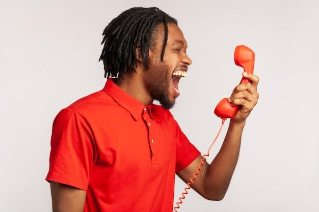 Retrato de hombre gritando y gritando hablando de teléfono fijo, quejándose de la calidad de la conexión.