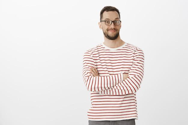 Retrato de hombre guapo agradable intrigado en gafas negras, sonriendo ampliamente