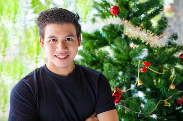 Retrato hombre guapo con árbol de navidad