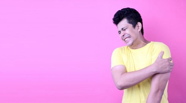 Retrato de un hombre guapo de asia, sosteniendo su hombro dolorido sobre fondo rosa en studio