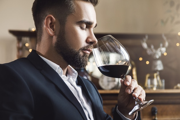 Retrato de hombre guapo con barba con una copa de vino tinto
