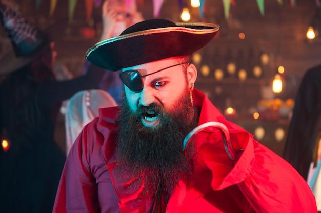 Retrato de hombre guapo con barba gritando y disfrazado de pirata en la celebración de halloween. bruja al fondo.