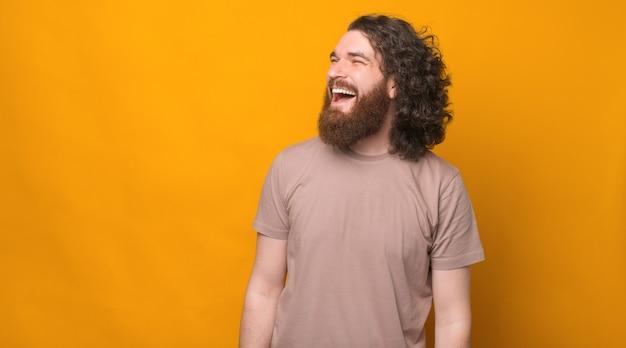 Retrato de hombre guapo con barba y pelo largo y rizado riendo sobre amarillo