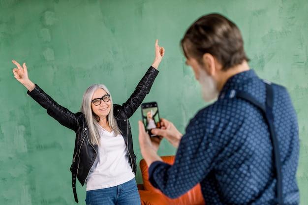 Retrato de hombre guapo con barba senior tomando fotos de su bella mujer, posando para la cámara sobre fondo de pared verde, sonriendo