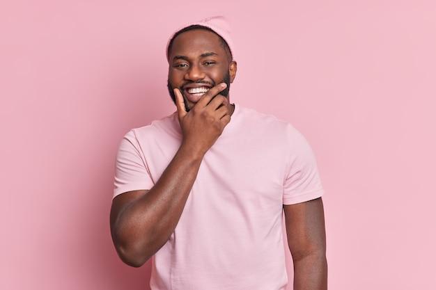 Retrato de hombre guapo con barba sostiene la barbilla sonríe ampliamente estando de buen humor