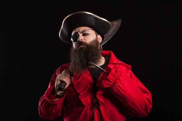 Retrato de hombre guapo con barba en un traje de pirata mirando seriamente a la cámara para halloween. hombre disfrazado de pirata caribeño.