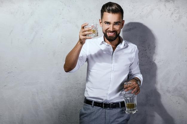 Retrato de hombre guapo con barba con un vaso de whisky
