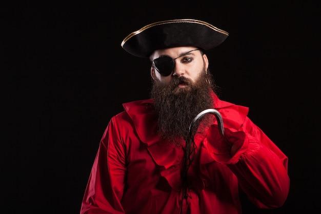 Retrato de hombre guapo con barba vestido con ropa de pirata medieval para el carnaval de halloween. hombre en traje de pirata aislado sobre fondo negro.
