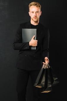 Retrato de hombre guapo con bolsas de compras
