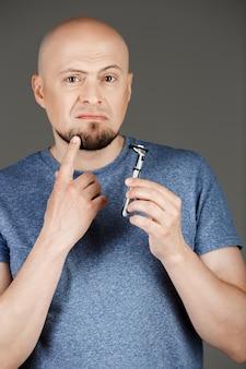 Retrato de hombre guapo en camisa gris con maquinilla de afeitar sobre pared oscura