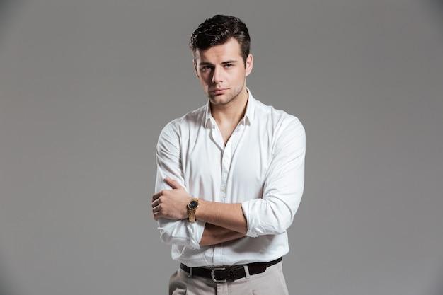 Retrato de un hombre guapo centrado en camisa blanca posando