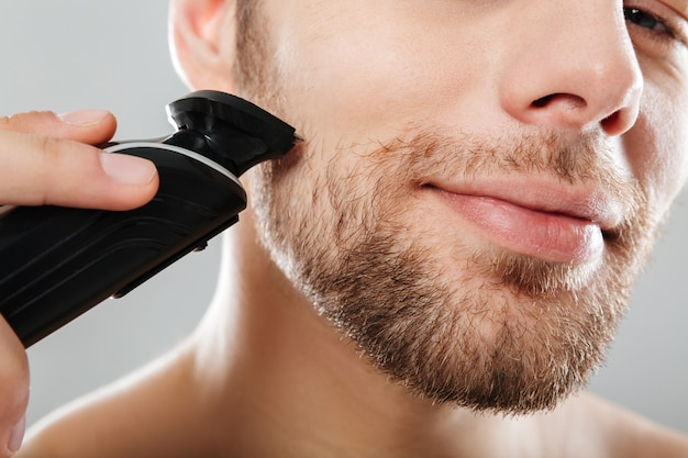 Retrato de hombre guapo contento y feliz mientras se afeita la piel con una máquina de afeitar eléctrica en la mañana contra la pared gris