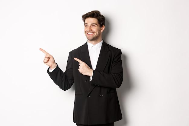 Retrato de hombre guapo exitoso en traje, apuntando y mirando hacia la izquierda con una sonrisa complacida, mostrando pancarta promocional, de pie sobre fondo blanco.