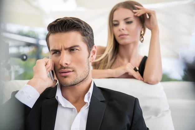 Retrato de un hombre guapo hablando por teléfono al aire libre en un restaurante con una mujer en la pared