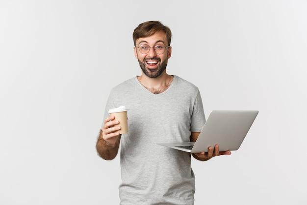 Retrato de hombre guapo independiente, tomando café y trabajando con un portátil