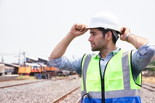 Retrato de hombre guapo ingeniero usar casco antes de trabajar en frente del garaje del tren
