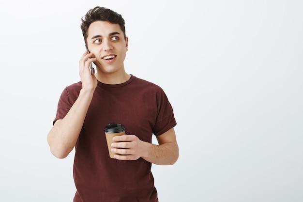 Retrato de hombre guapo intrigado en camiseta roja hablando por teléfono