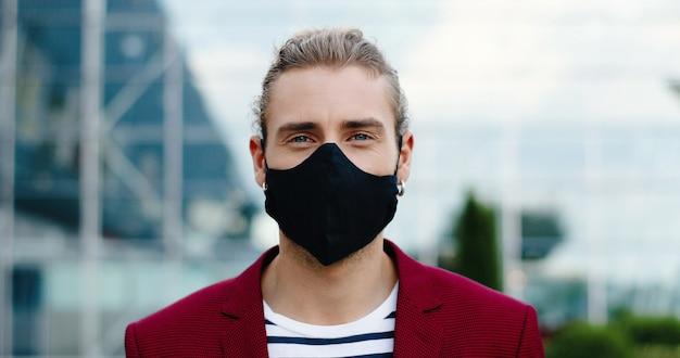 Retrato de hombre guapo joven caucásico en máscara mirando a cámara al aire libre. cerca de la cara del hombre guapo elegante con aretes en las orejas en la calle. concepto de pandemia de coronavirus. distancia social