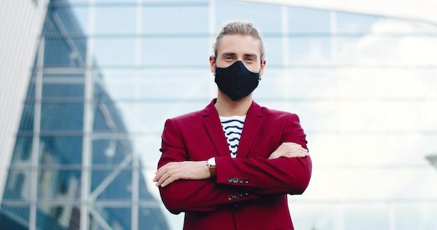 Retrato de hombre guapo joven caucásico en máscara mirando a cámara con cara sonriente y cruzando las manos al aire libre. hombre guapo con estilo en la calle. concepto de pandemia de coronavirus. distancia social.