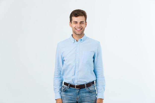 Retrato de hombre guapo de moda feliz en jeans y camisa azul mira a cámara.
