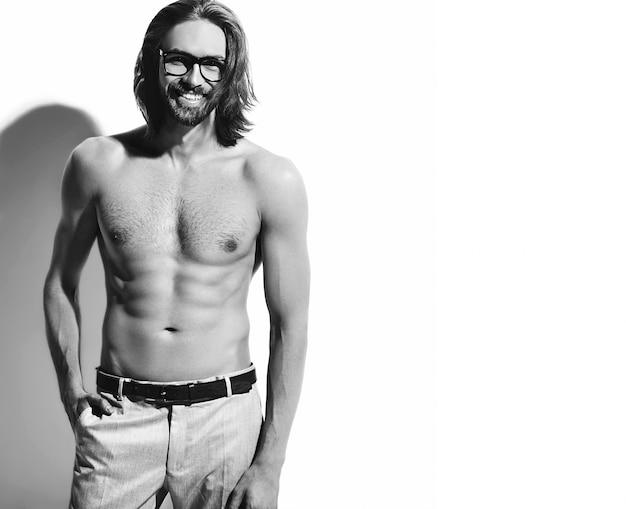 Retrato de hombre guapo modelo hipster moda elegante con el pecho desnudo en gafas en blanco. con una mano en el bolsillo