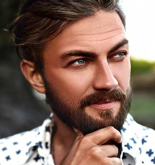Retrato de hombre guapo modelo de moda con ropa de camisa blanca posando en la calle