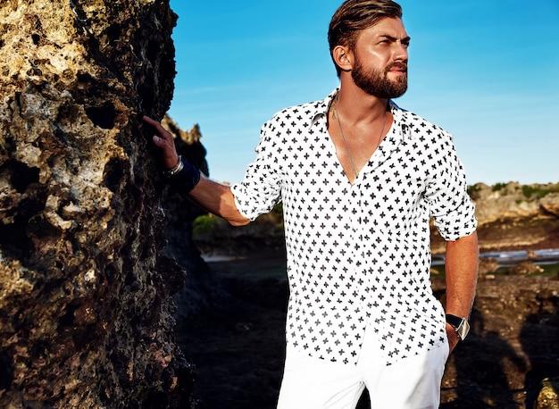 Retrato de hombre guapo modelo vistiendo ropa blanca posando cerca de rocas en la playa en el cielo azul