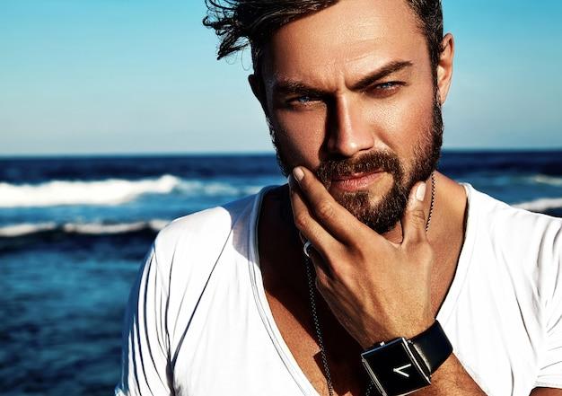 Retrato de hombre guapo modelo vistiendo ropa blanca posando en mar azul