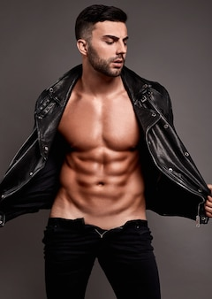 Retrato de hombre guapo musculoso en chaqueta de cuero en pared gris