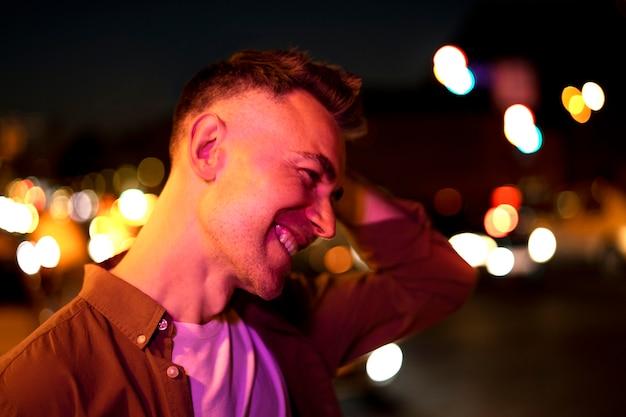 Retrato de hombre guapo por la noche en las luces de la ciudad