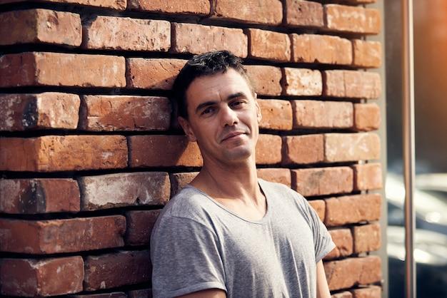 Retrato de hombre guapo de pie en la calle cerca de la pared de ladrillo
