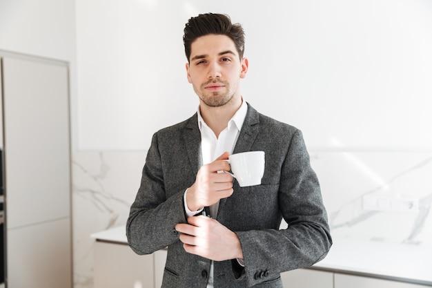 Retrato de hombre guapo en ropa profesional mirando a la cámara y sosteniendo una taza de café a la hora del almuerzo en casa