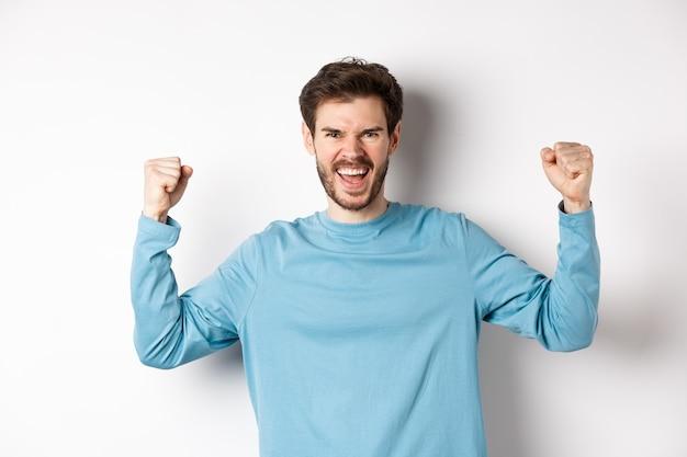 Retrato de hombre guapo satisfecho ganador del premio, regocijándose en el triunfo, celebrando la victoria y gritando sí, de pie sobre fondo blanco.