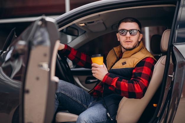 Retrato de hombre guapo sentado en el coche y tomando café
