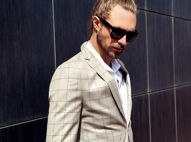 Retrato de hombre guapo sexy vestido con elegante traje a cuadros beige
