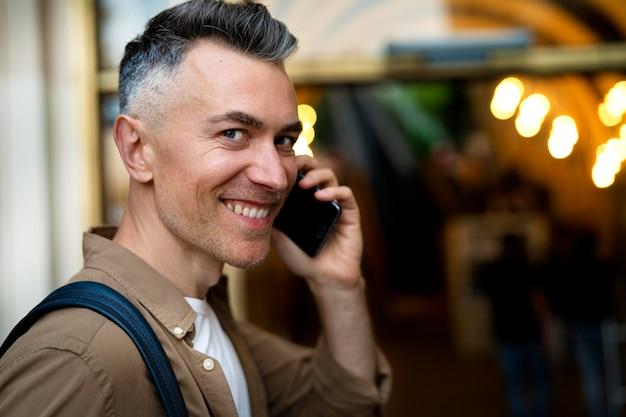 Retrato de hombre guapo con smartphone en la ciudad