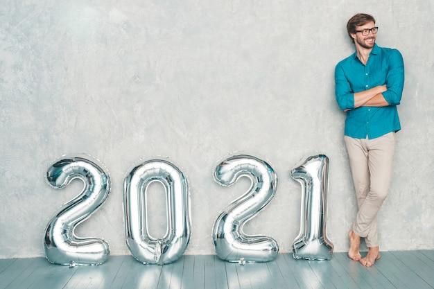 Retrato de hombre guapo sonriente posando junto a la pared. hombre barbudo sexy staning cerca de silver 2021 balloons. feliz año nuevo 2021. números metálicos 2021