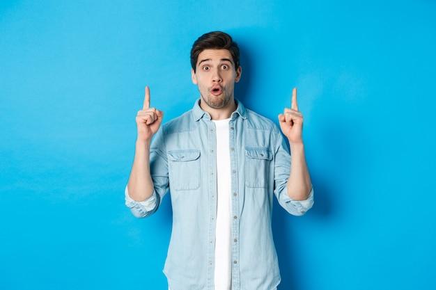Retrato de hombre guapo sorprendido apuntando con el dedo hacia arriba, mostrando el logo sobre fondo azul.
