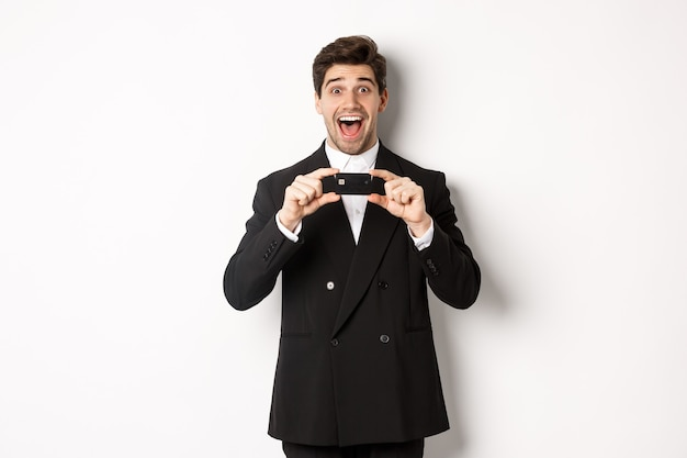 Retrato de hombre guapo sorprendido en traje negro, mostrando la tarjeta de crédito y recomendando el banco, de pie sobre fondo blanco.