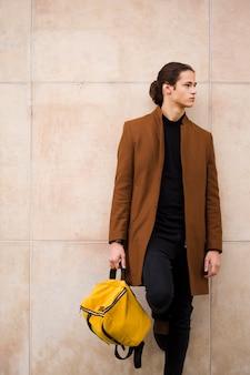 Retrato de hombre guapo sosteniendo una bolsa