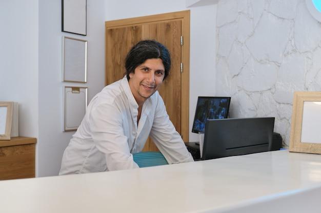 Retrato de hombre guapo trabajando en la recepción en el hotel resort