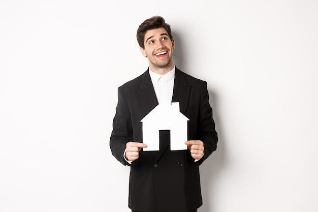 Retrato de hombre guapo en traje buscando casa, sosteniendo la casa de papel y mirando la esquina superior derecha soñadora, de pie sobre fondo blanco.