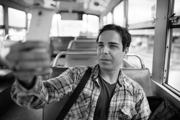 Retrato de hombre guapo turista persa pasar vacaciones y explorar la ciudad de bangkok en blanco y negro