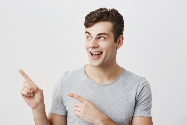 Retrato del hombre hermoso caucásico que tiene una sonrisa amplia que lleva la camiseta gris que presenta señalando con los dedos índices en el espacio blanco de la copia para el contenido publicitario o promocional.